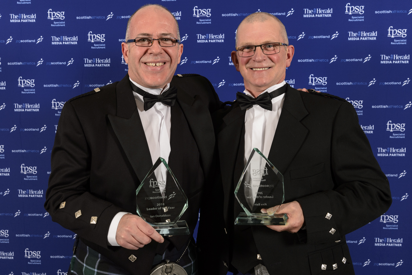 Alex Bain and Ian Donaldson, in kilts, jackets and bow ties, holding their awards