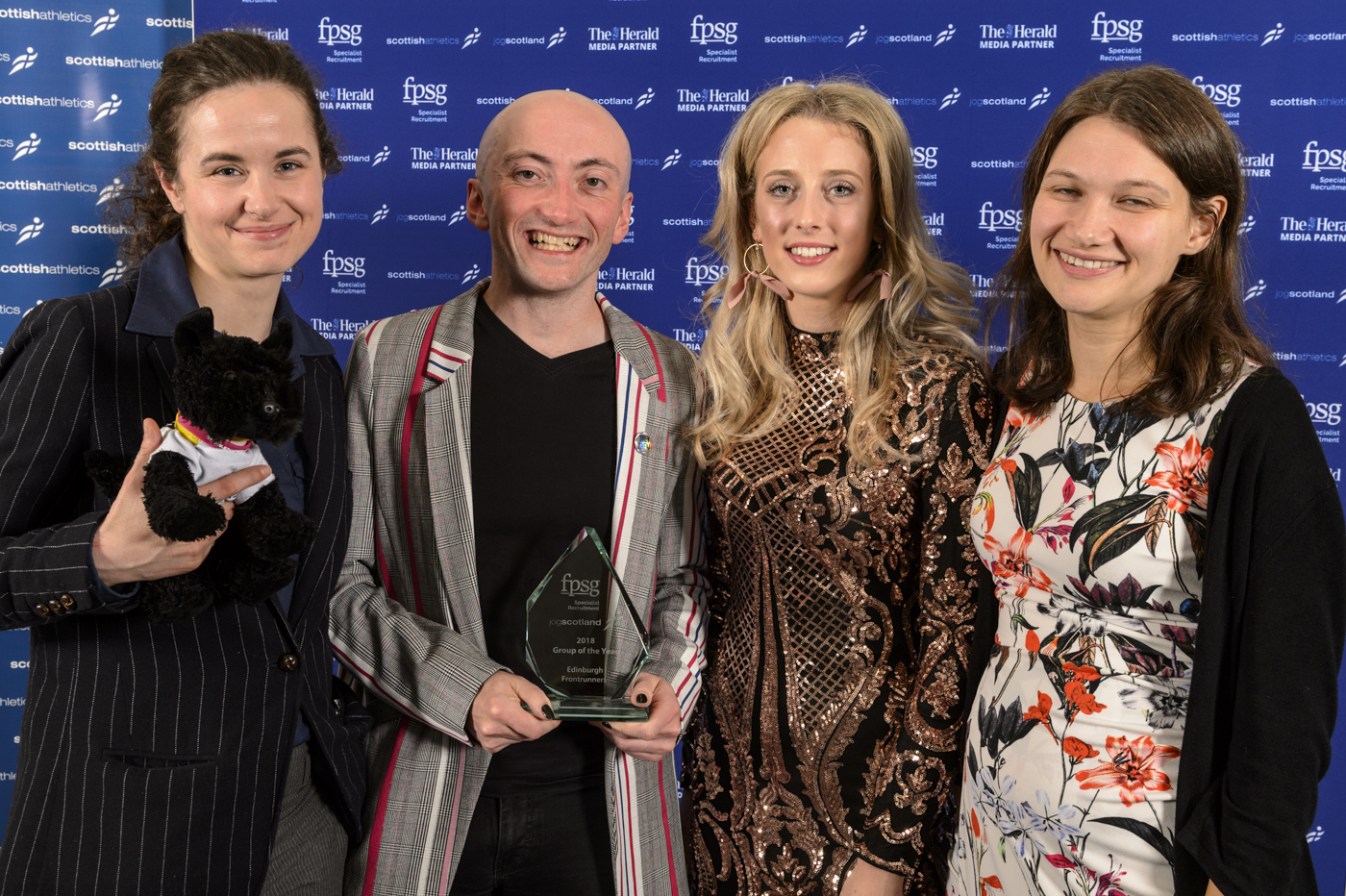 Three members of Edinburgh Frontrunners, with athlete Jemma Reekie, all in smart suits and dresses, holding their award