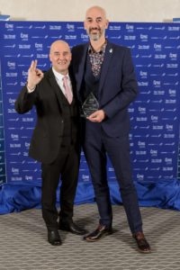 The two representatives of Jog Con, in suits, holding their award