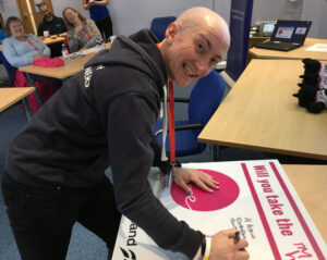 "Al is leaning on a table, signing a large white board that says ""Will you take the I'm here pledge"". He's signing it with a marker pen, smiling up at the camera"